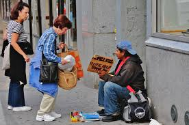 An act of prosocial behaviour, where a woman gives money to a homeless man